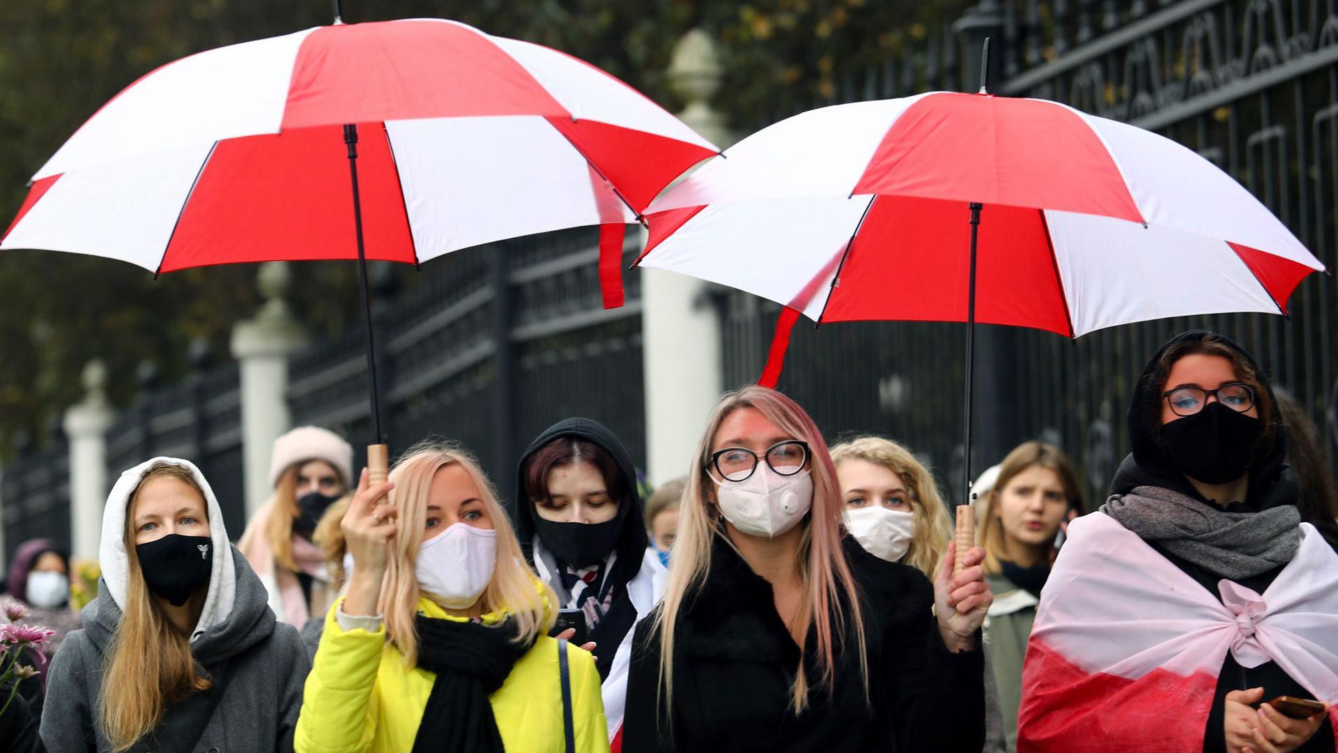Frauen demonstrieren am Samstag mit Regenschirmen in den Farben der historischen Nationalflagge von Belarus in Minsk.