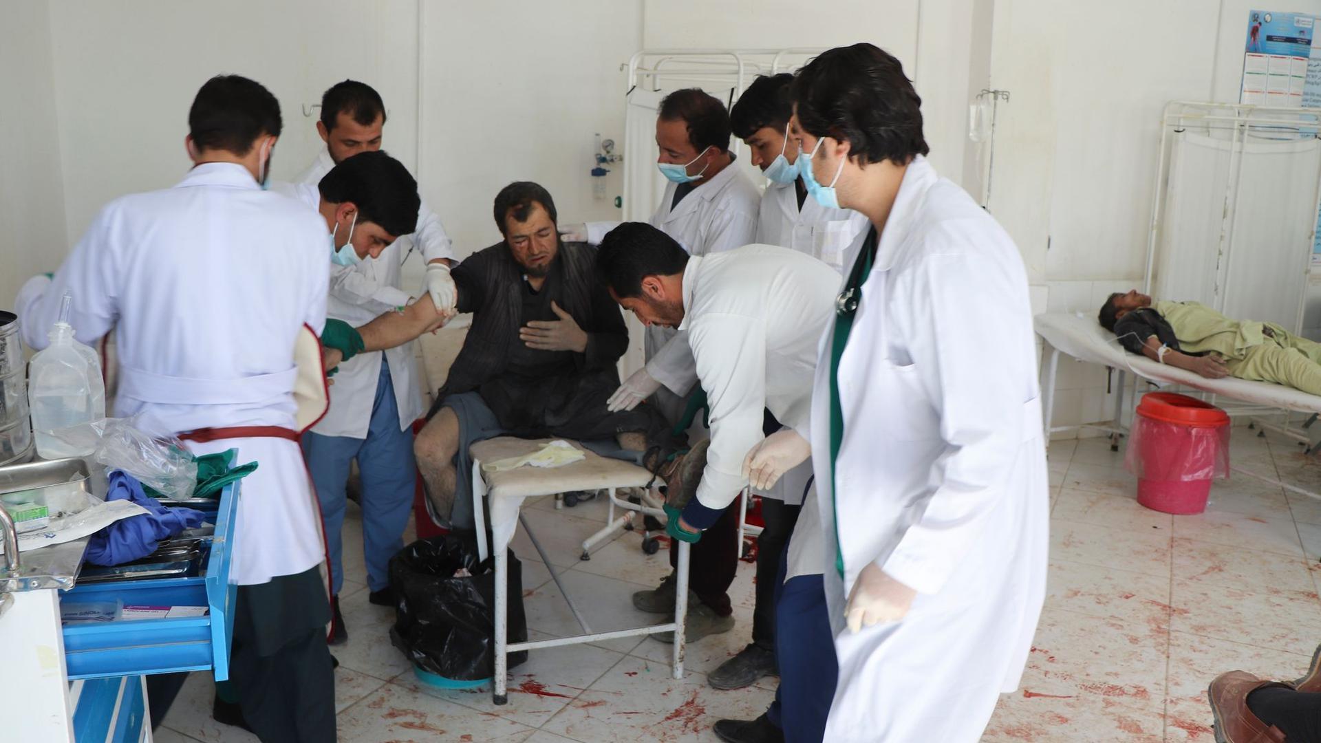 Ärzte behandeln einen Mann nach dem Anschlag in der Provinz Ghor.
