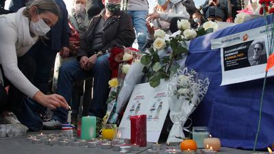 Eine Frau zündet eine Kerze an: Zahlreiche Menschen haben sich nach der brutalen Ermordung eines Lehrers am Wochenende zu einer Solidaritätsdemonstration in Paris versammelt.