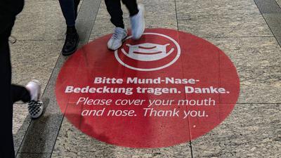 """Der Aufkleber """"Bitte Mund-Nase-Bedeckung tragen. Danke"""" ist im Bahnhof am Alexanderplatz in Berlin auf dem Boden befestigt."""