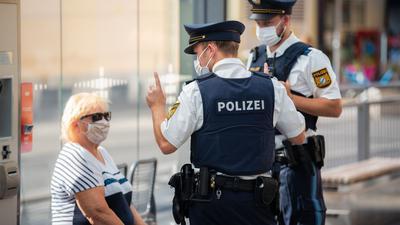 Zwei Polizisten nehmen an einer Tram-Haltestelle in Würzburg von einer Frau nach einem Verstoß gegen die Maskenpflicht im öffentlichen Nahverkehr die Personalien auf.