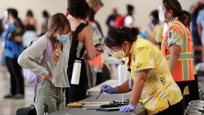 Eine Reisende auf Hawaii lässt sich vor einemTest beraten.