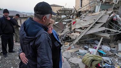 Ein Paar steht vor den Trümmern eines zerstörten Hauses in Berg-Karabach.