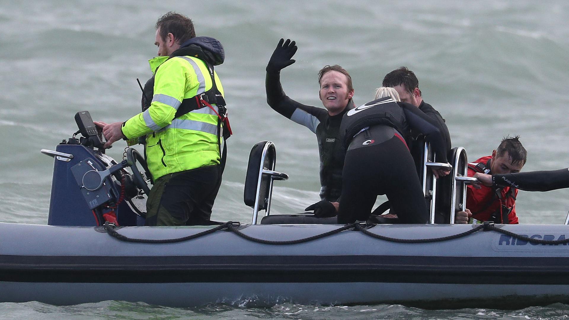 John Bream, ehemaliger Fallschirmspringer aus Großbritannien, winkt aus einem Boot, das ihn nach seinem Sprung aus etwa 40 Metern Höhe ins Meer geborgen hat.