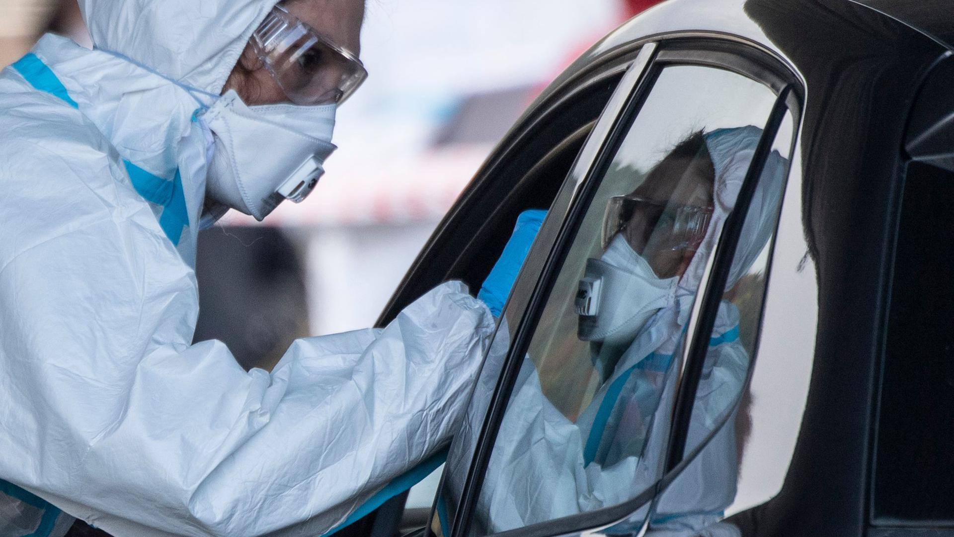 Ein Mitarbeiter eines Corona-Testzentrums auf dem Marburger Messegelände nimmt einen Abstrich von einem Autofahrer.