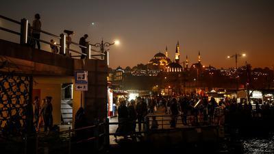 Menschen schlendern vor der Kulisse der Süleymaniye-Moschee am Ufer des Bosporus entlang. Die Zahl der Corona-Fälle in der Türkei steigt weiter an.