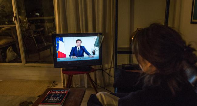 Eine Frau verfolgt in Paris die TV-Ansprache von Staatspräsident Emmanuel Macron.