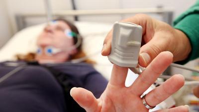 Eine Schlafpatientin wird von einem Krankenpfleger im Schlaflabor der Kliniken Essen-Mitte an Elektroden angeschlossen.