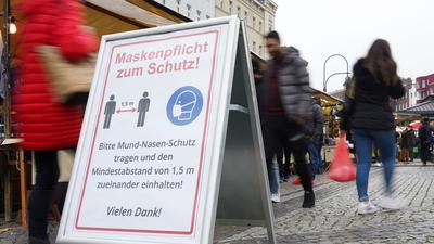 Ein Schild weist auf einem Wochenmarkt in Berlin auf Maskenpflicht und Abstandsgebot hin.
