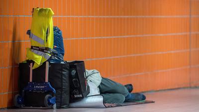 Ein Obdachloser schläft in einer Unterführung.
