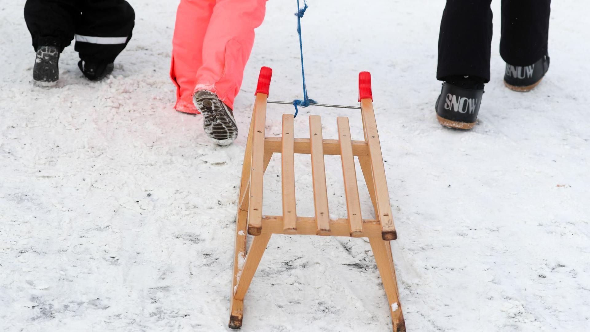 Winterurlauber gehen mit einem Schlitten zu einer Rodelbahn. NRW erwägt erneut eine Verlängerung der Winterferien.