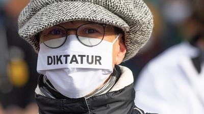 """""""Diktatur"""" steht auf der Nase-Mund-Bedeckung"""" einer Teilnehmerin an einer """"Querdenken""""-Demonstration in Frankfurt am Main."""