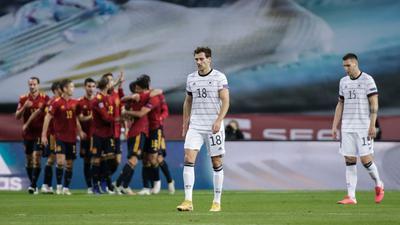 Während Spaniens Spieler einen Treffer feiern lassen Leon Goretzka (M) und Niklas Süle (r) enttäuscht den Kopf hängen.