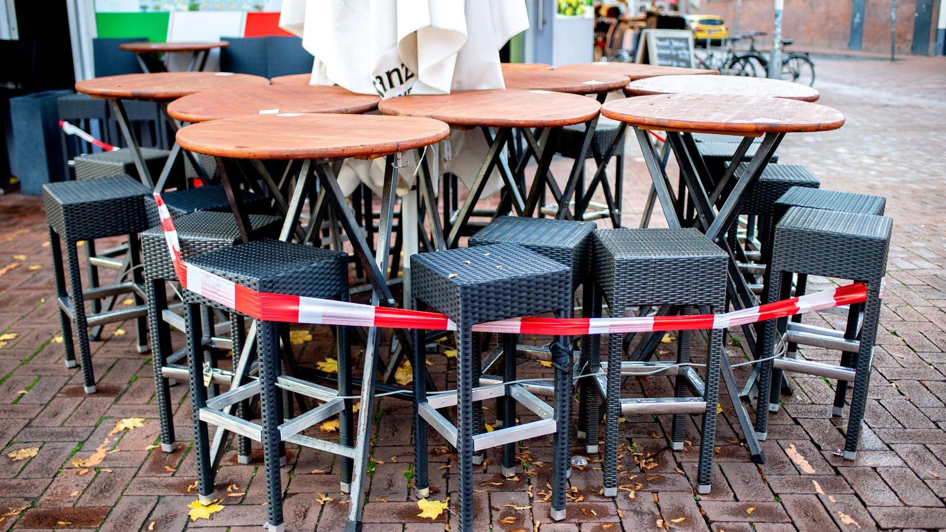 Tische und Stühle stehen vor einer Pizzeria im Hannover. Die Verlängerung des Teil-Lockdowns in Deutschland bis kurz vor Weihnachten ist so gut wie sicher.