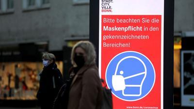 Frauen stehen neben einem Hinweisschild zur Maskenpflicht an einer Haltestelle inBonn. Die Länder fordern vor den Beratungen mit Kanzlerin Merkel strengere Kontaktbeschränkungen, um die hohen Coronazahlen zu senken.