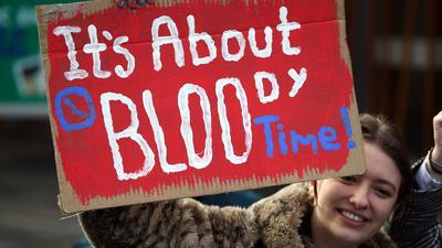 """Eine Frau in Edinburgh hält bei einer Kundgebung ein Schild mit der Aufschrift """"It's about bloody time!"""" (dt. Es ist verdammt noch mal an der Zeit) hoch."""