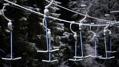 Bügel eines Schleppliftes hängen in schneebedeckter Landschaft. Wegen der Maßnahmen um das Coronavirus müssen Skilifte geschlossen bleiben.
