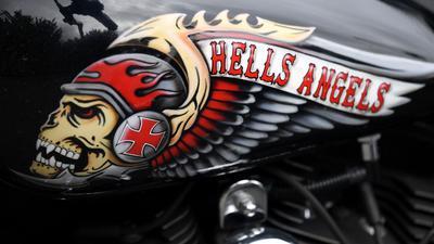 Das Hells Angels-Emblem, ein Totenkopf mit Helm und Flügeln, auf einem Tank eines abgestellten Motorrads.
