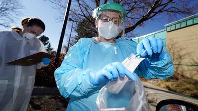 In der US-Stadt Denver führen zwei Gesundheitsmitarbeiterinnen bei einem Patienten einen Corona-Test durch.