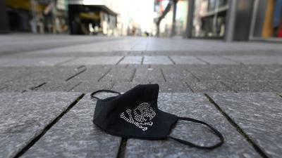 Ein verlorener Mundschutz liegt auf einer Einkaufsstraße.