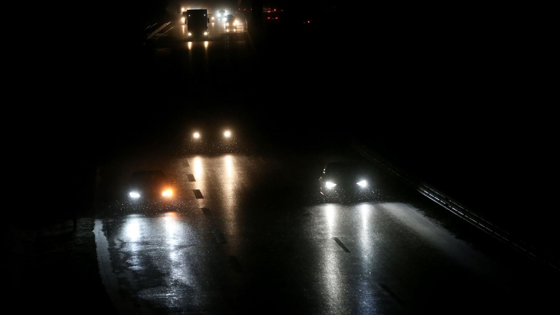 Autos fahren am frühen Morgen auf der Bundesstraße 16 im Schneetreiben.