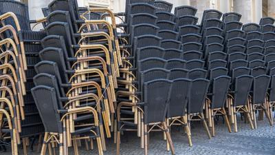 Zusammengestellte Stühle stehen vor einem gastronomischen Betrieb in Potsdam.