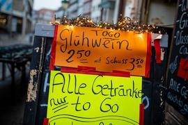 """Glühwein """"to go"""" bewirbt eine Kneipe in der Altstadt in Hannover auf einem Werbeaufsteller."""