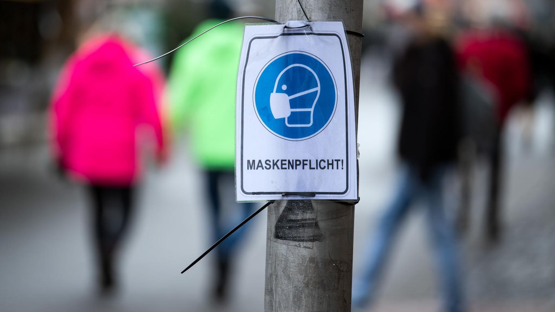 Ein Schild, auf dem Fußgänger zum Tragen eines Mund-Nasen-Schutzes aufgefordert werden.