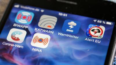 """Verschiedene Warn-Apps, darunter die Notfall-Informations- und Nachrichten-App """"NINA"""" des Bundesamts für Bevölkerungsschutz und Katastrophenhilfe, sind auf einem Smartphone zu sehen."""