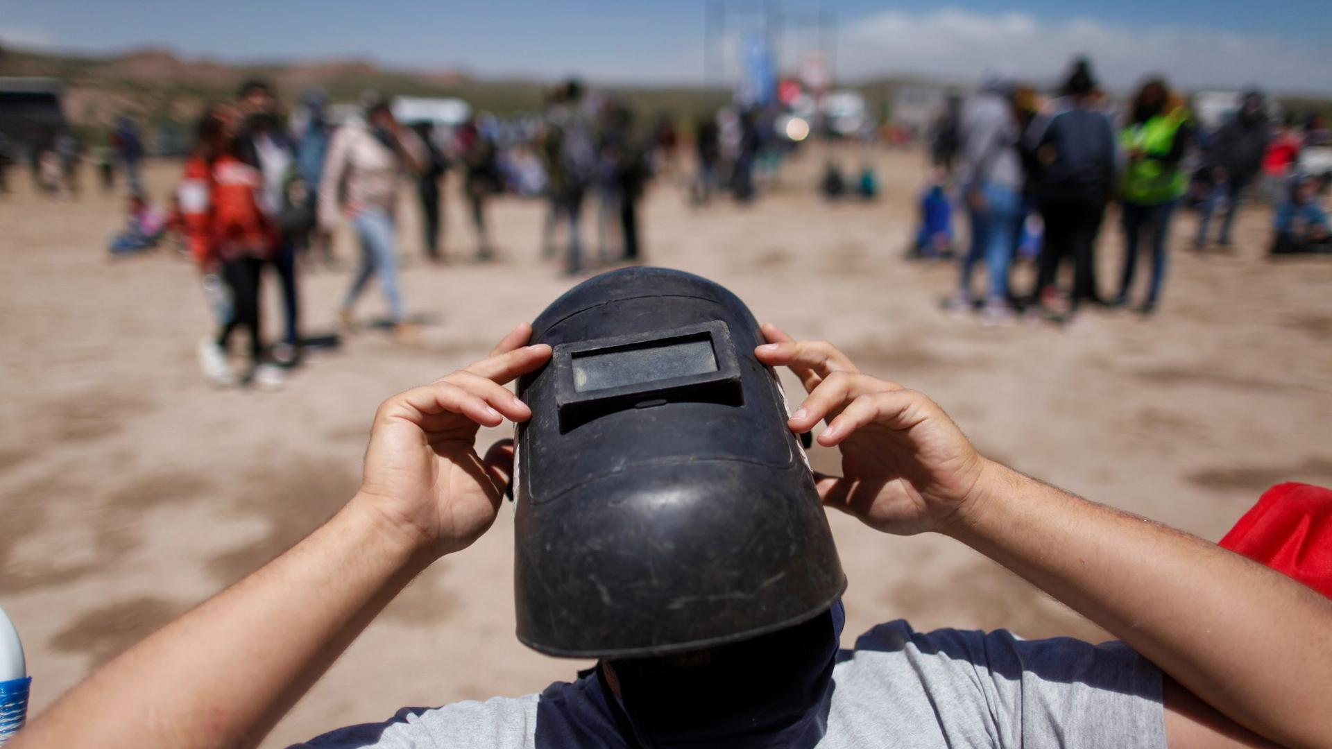 Mit einer Schweißermaske als Schutz wartet ein Mann im argentinischen Piedra Del Aguila auf eine totale Sonnenfinsternis.