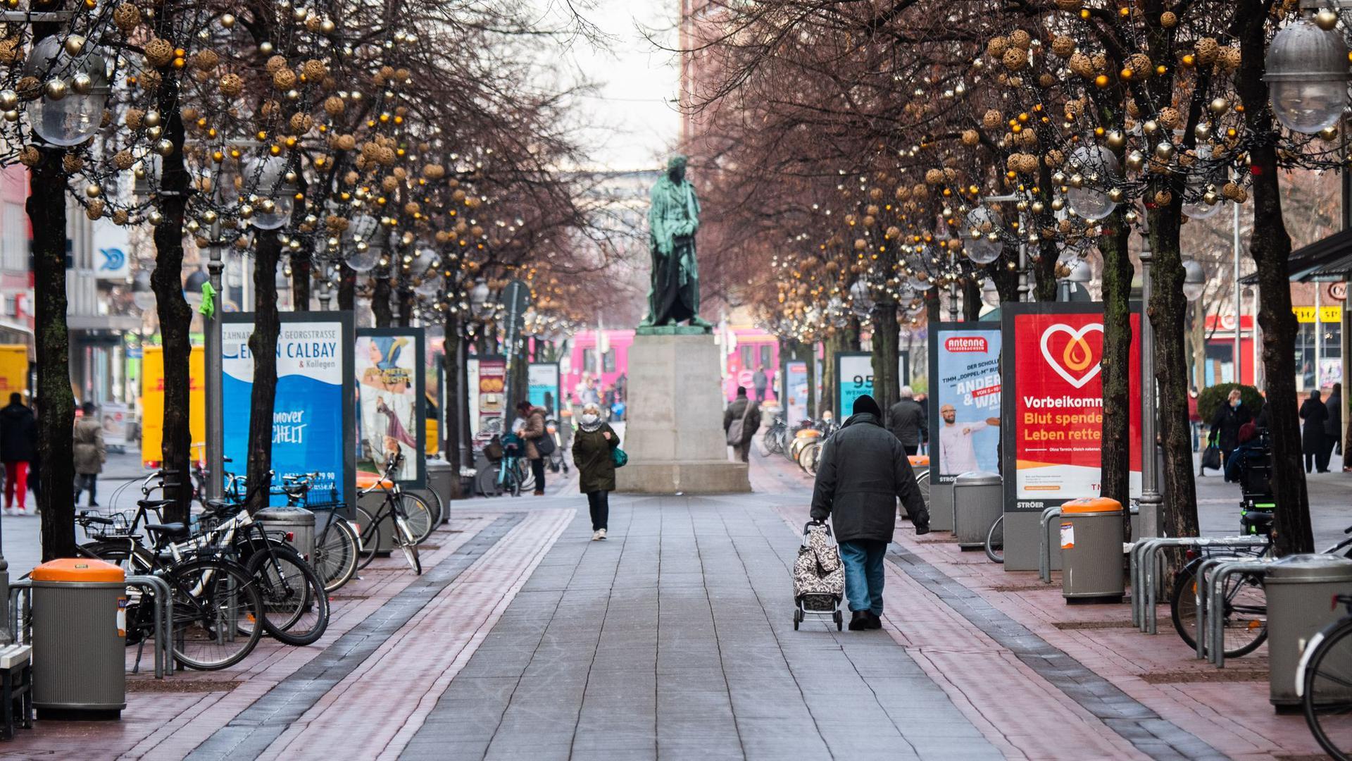 Passanten laufen durch die beinahe menschenleere Innenstadt vonHannover.