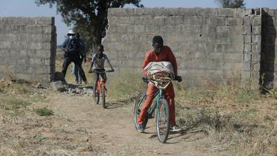 """Kinder fahren auf Fahrrädern durch ein Loch in einer Mauer der Schule """"Government Science Secondary School"""", das entstand, als bewaffnete Männer vor einigen Tagen Kinder aus der Schule entführten, und das nun bewacht wird."""
