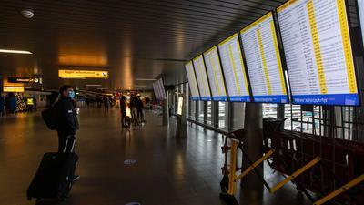 Ein Reisender schaut auf die Anzeigetafeln mit den Abflügen am Flughafen Schiphol bei Amsterdam.
