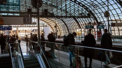 Reisende warten im Hauptbahnhof in Berlin auf einen Zug.