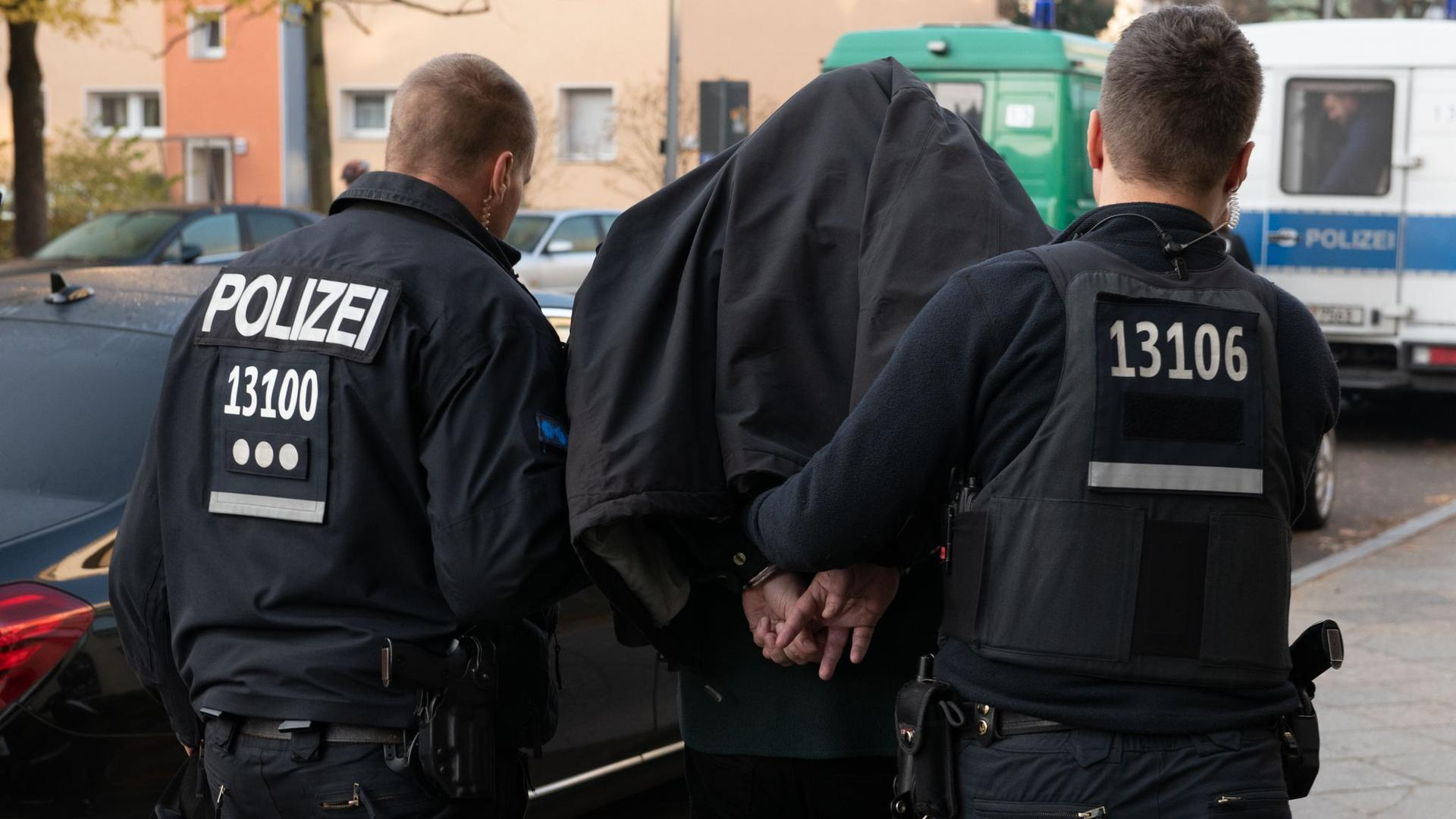 Polizeibeamte führen einen Mann nach einer Razzia in Berlin ab. Der Einsatz richtete sich gegen kriminelle Clan-Mitglieder.