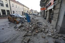 Trümmer eines durch ein Erdbeben eingestürzten Hauses bedecken ein Fahrzeug, das an einer Straße in Sisak steht.