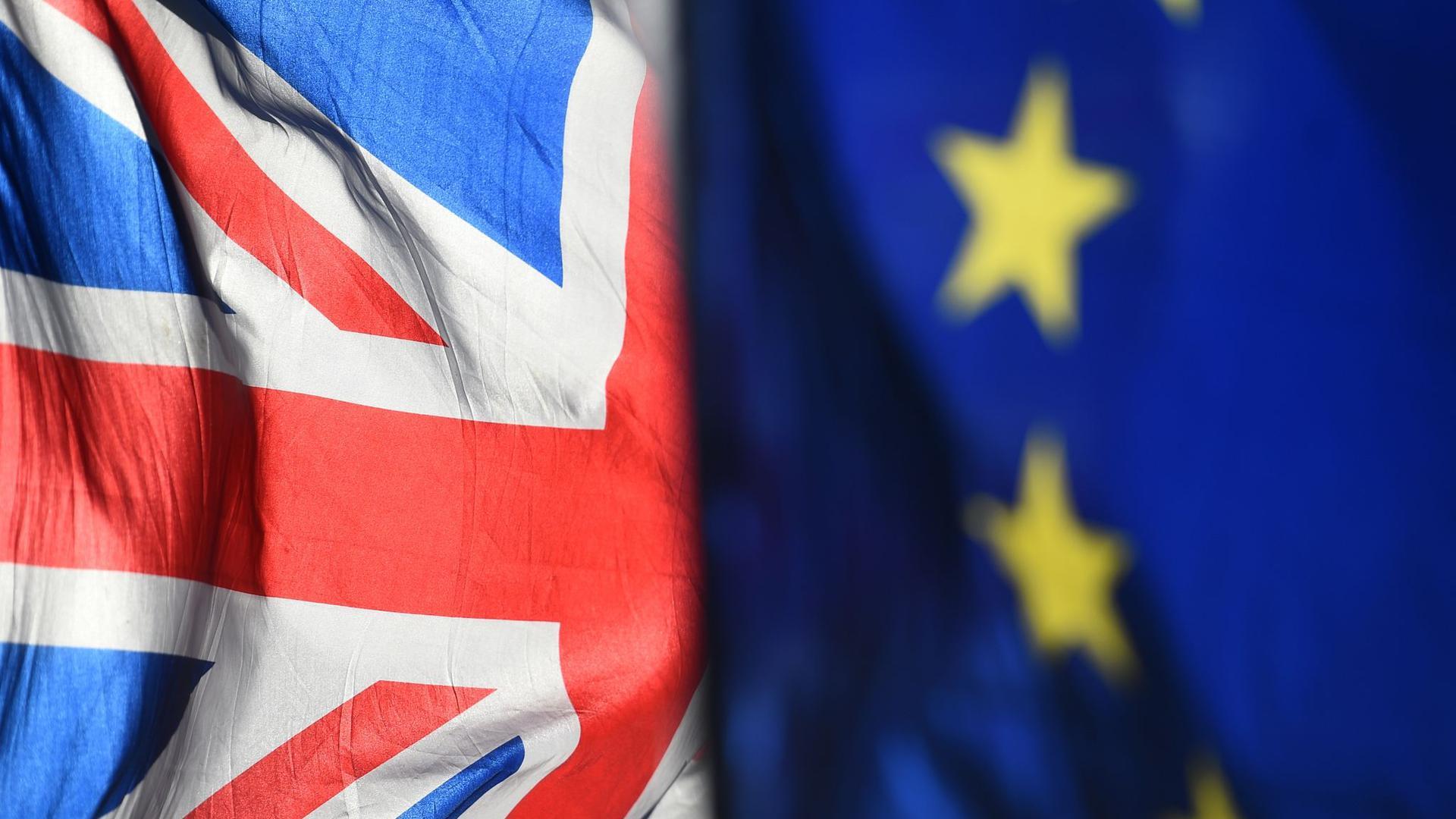 """Die Flagge der EU und der """"Union Jack"""" vor dem Parlament in Westminster."""