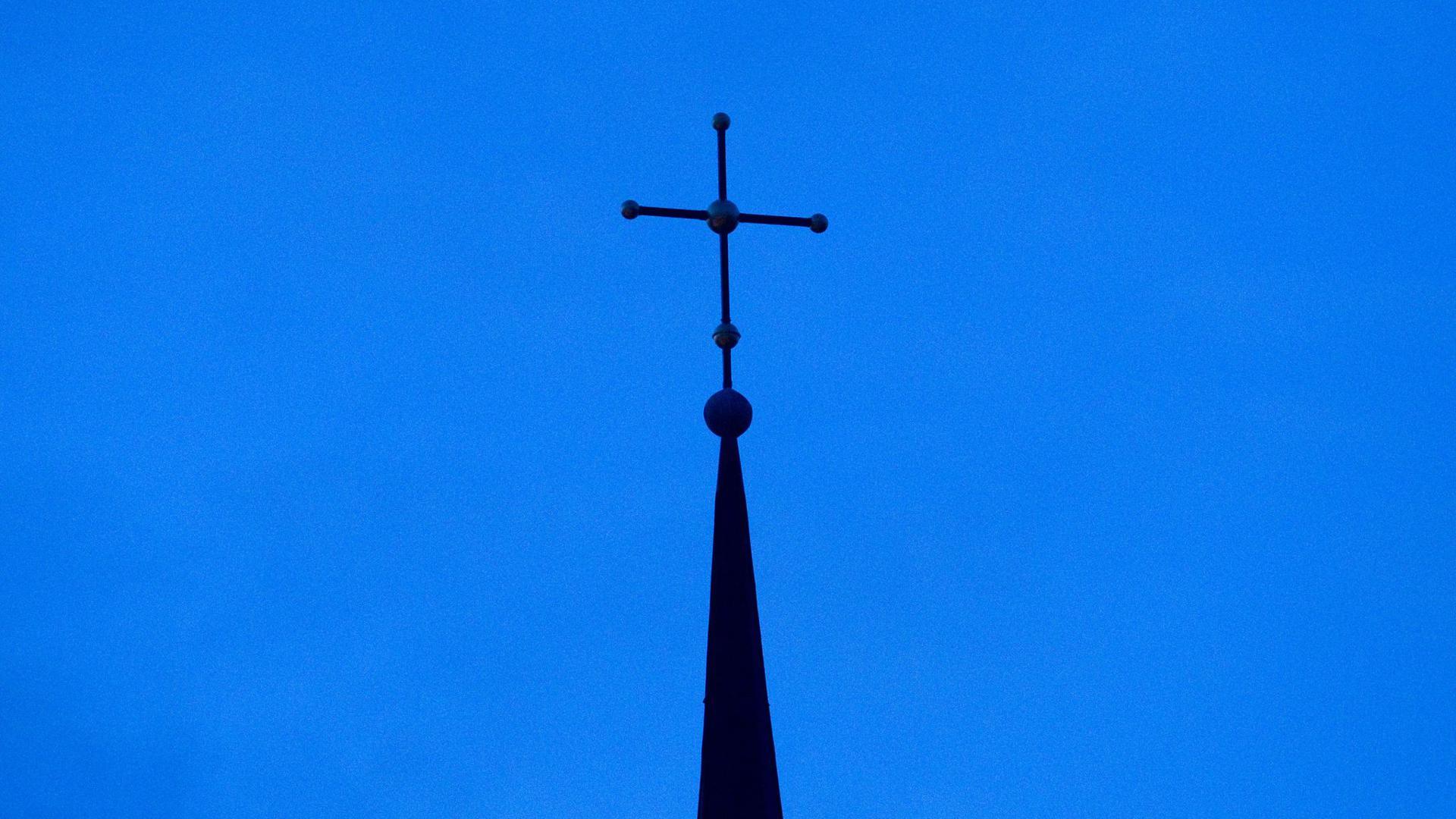 Das Kreuz einer evangelisch-lutherischen Kirche in der Abenddämmerung.