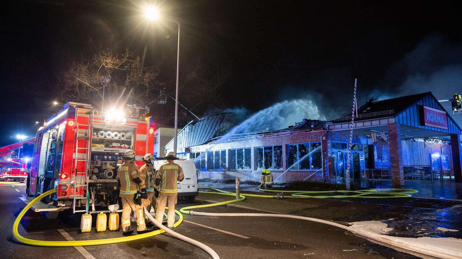 Feuerwehrleute löschen einen brennenden Supermarkt in Berlin.