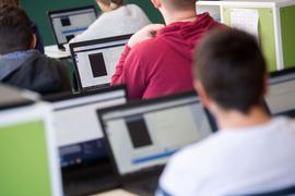 Schüler und Schülerinnen mit Laptops im Unterricht.