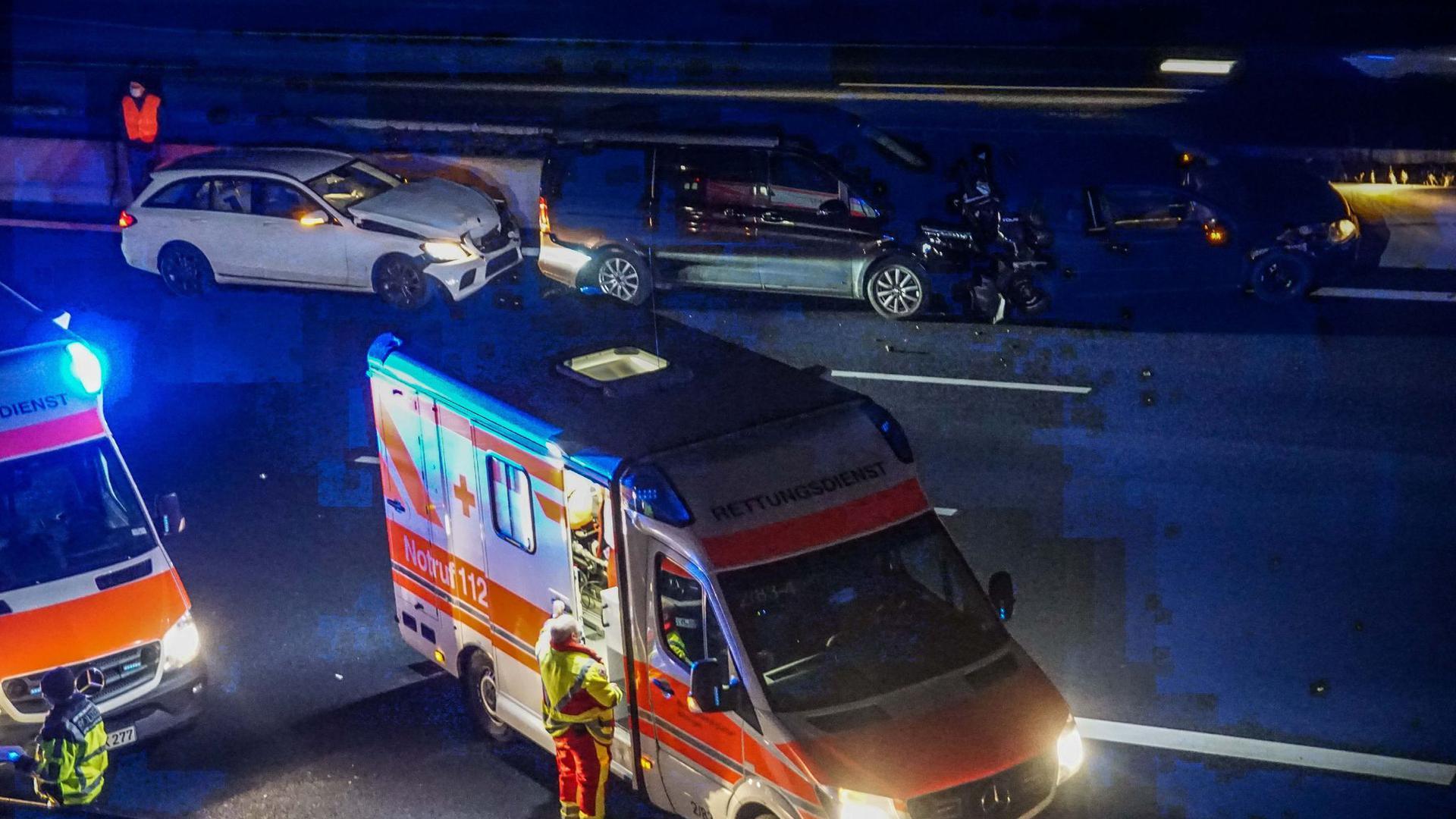 Rettungskräfte arbeiten an einer Unfallstelle mit mehreren PKWs auf der A8.