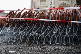 Auf dem Gendarmenmarkt in Berlin stehen zusammengestapelte Stühle hinter einem Absperrband.