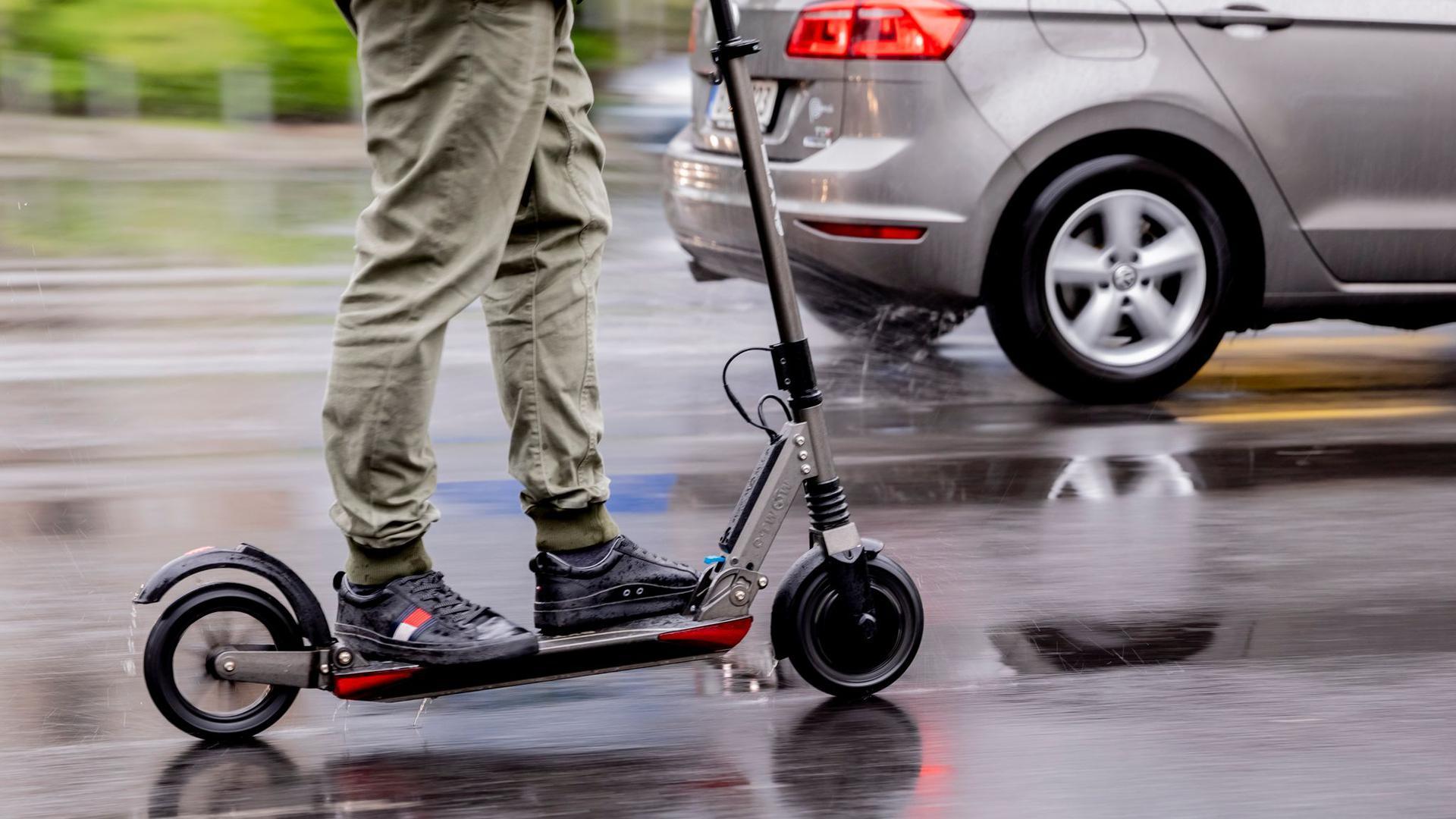 Ein Mann fährt mit einem E-Scooter auf der Straße.