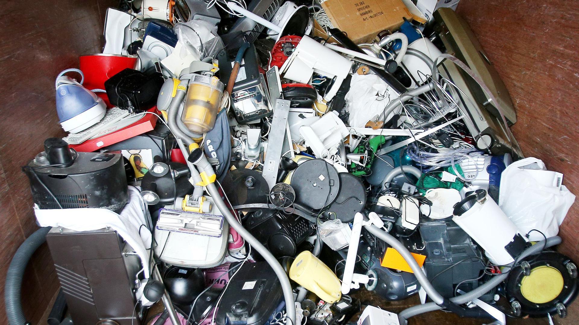 Ausrangierte Haushaltsgeräte und andere Elektrogeräte in einem Sammelbehälter für Elektroschrott.