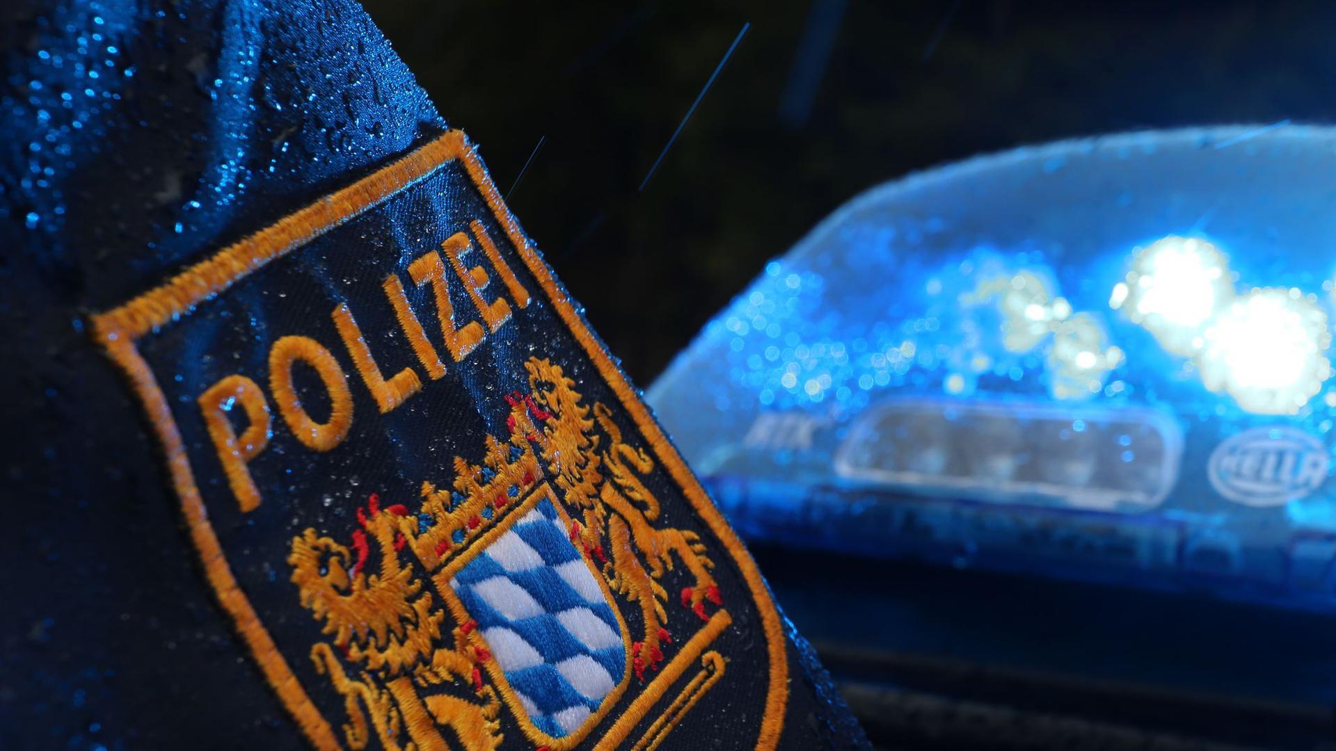 Der Arm eines Polizisten neben dem Blaulicht eines Polizeiautos.