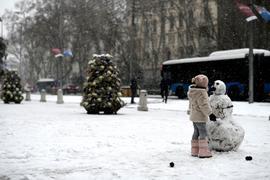 Ein Mädchen baut auf einer Straße in Madrid einen Schneemann.