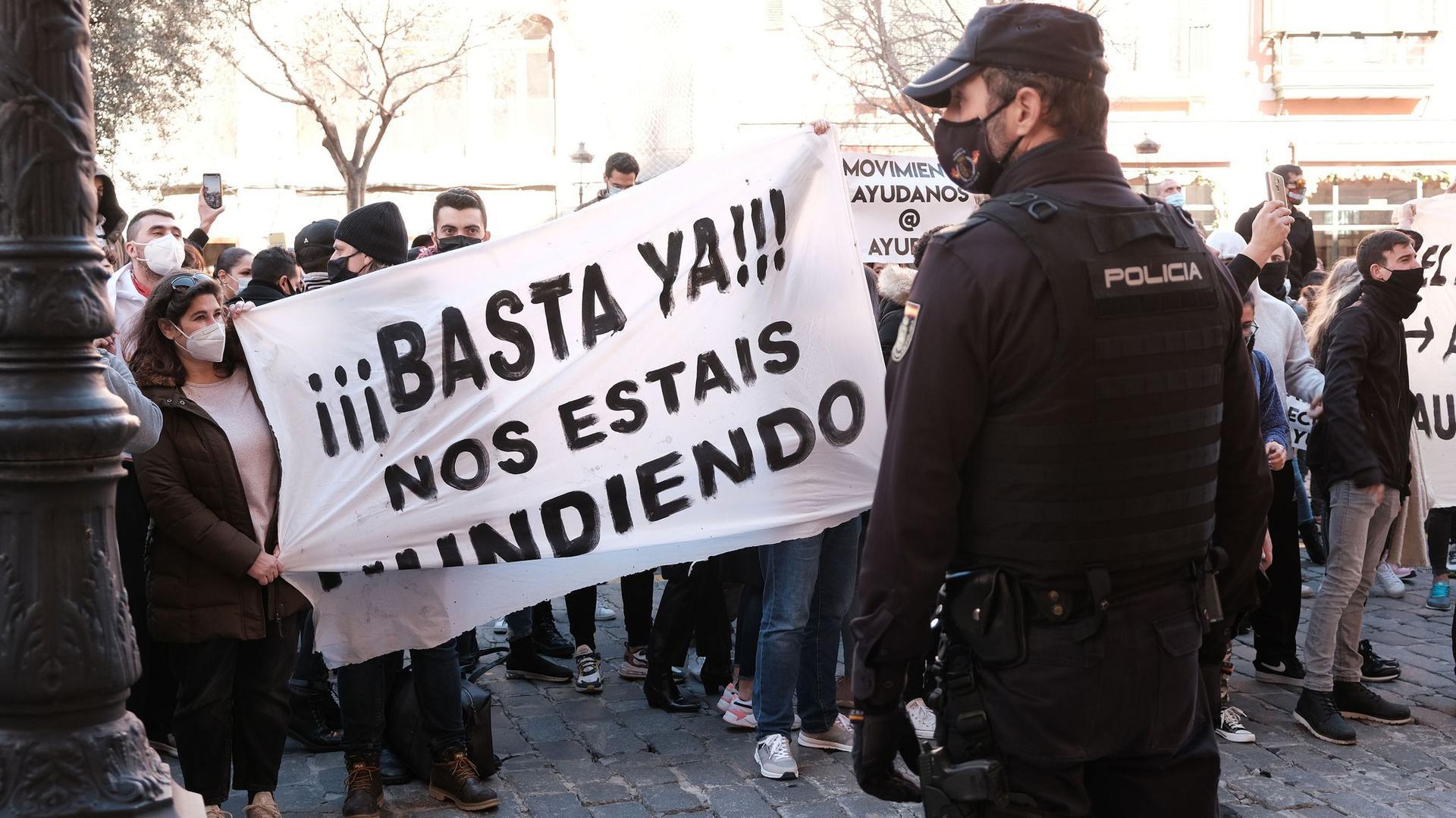 """""""Schluss damit, ihr ruiniert uns"""" steht auf einem Banner, das Demonstranten während einer Kundgebung vor dem Consolat de Mar halten, dem Sitz der Regierung der Balearen in Palma de Mallorca."""