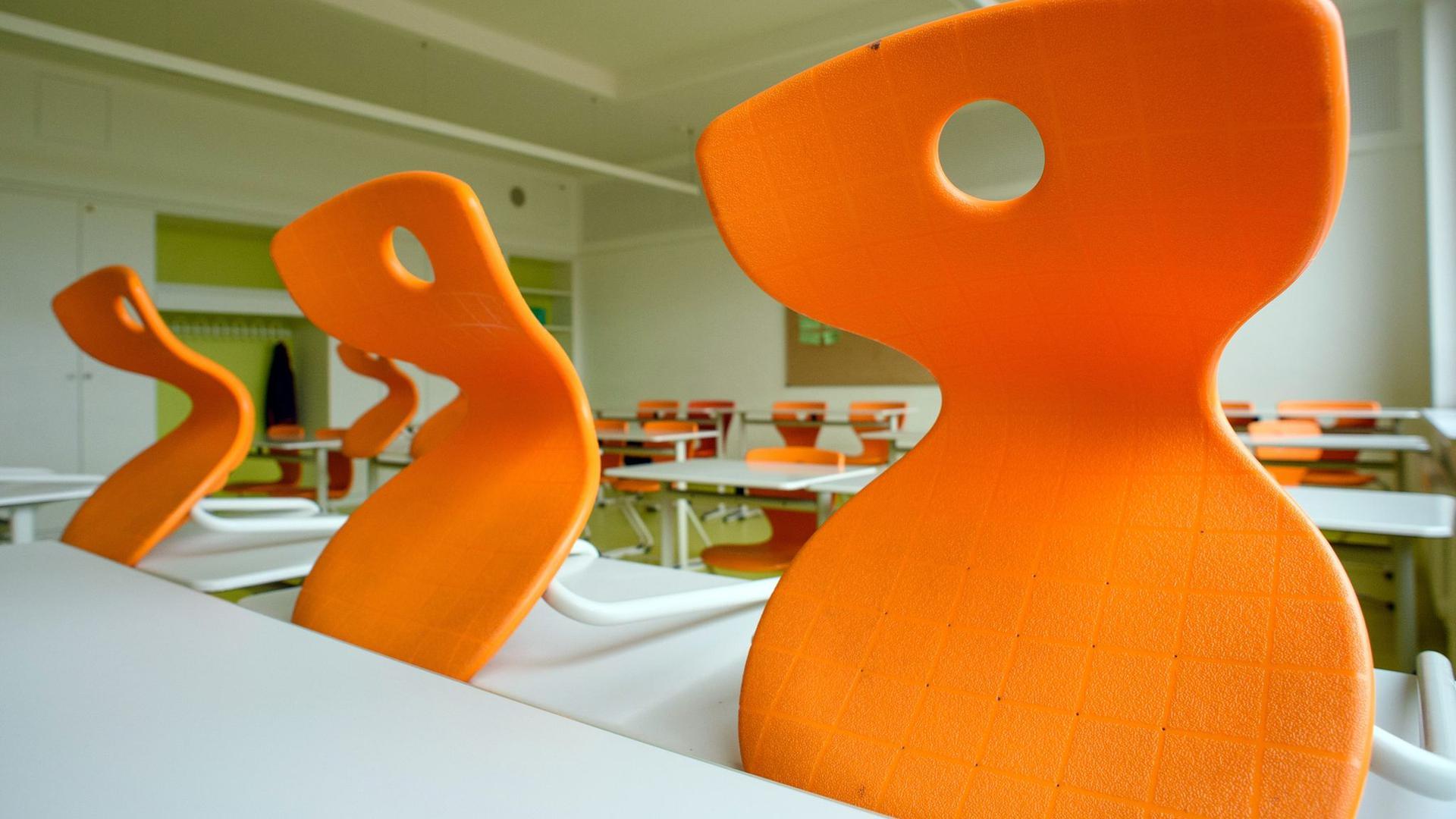 Ein leeres Klassenzimmer mit orangefarbenen Stühlen.