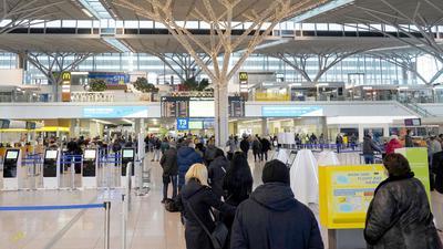 Flugpassagiere stehen in Schlangen im Flughafengebäude vor der Abfertigung.
