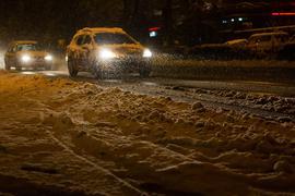 Autos sind in Freiburg im dichten Schneetreiben unterwegs.